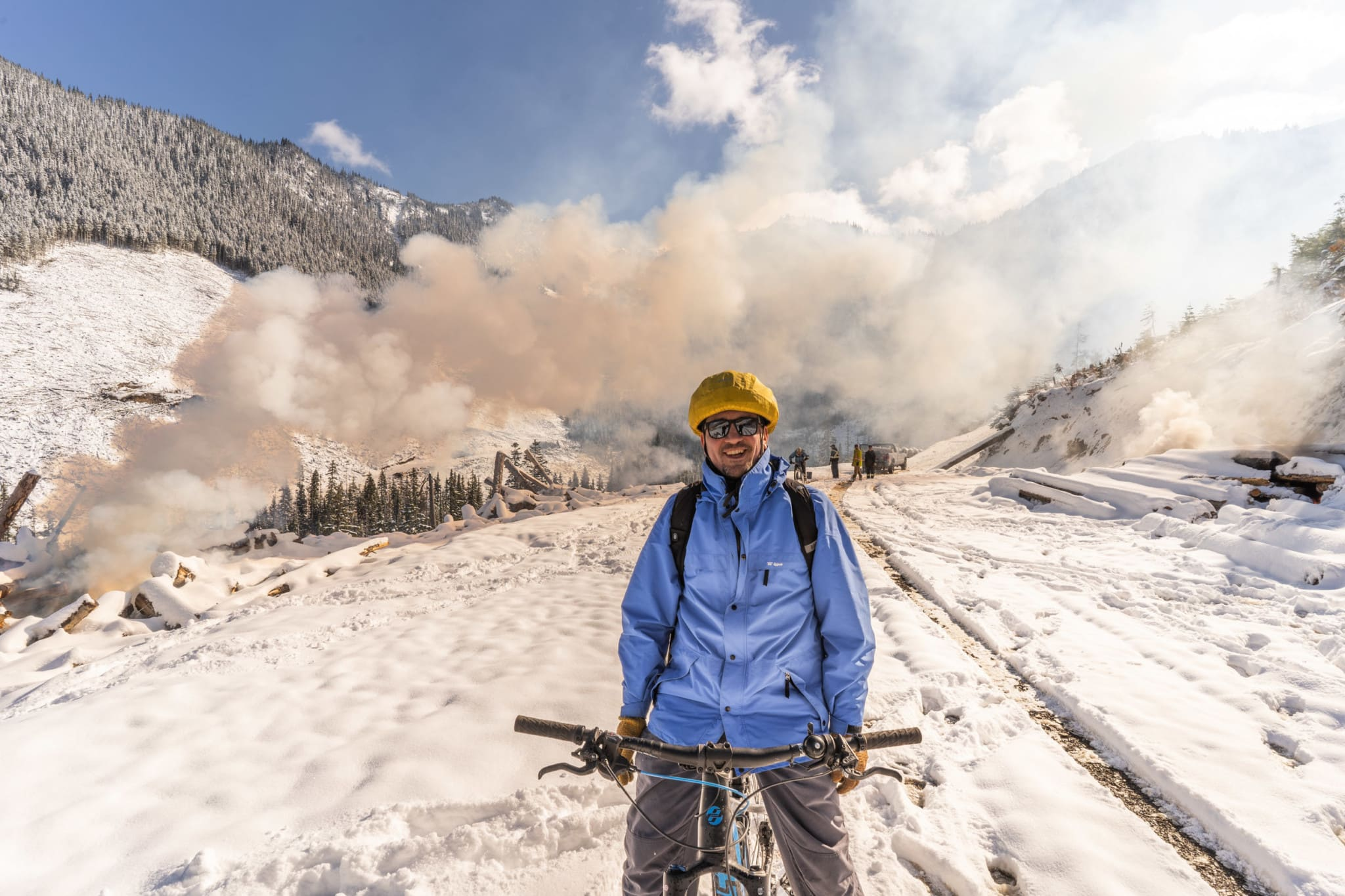 Author Chris Pollon rides an electric bike in the Manning Park 'Doughnut Hole.' Slash piles from recent clearcut logging on East Point Mountain are being burned by forestry company contractors, sending great plumes of smoke into the sky. Photo: Fernando Lessa / The Narwhal