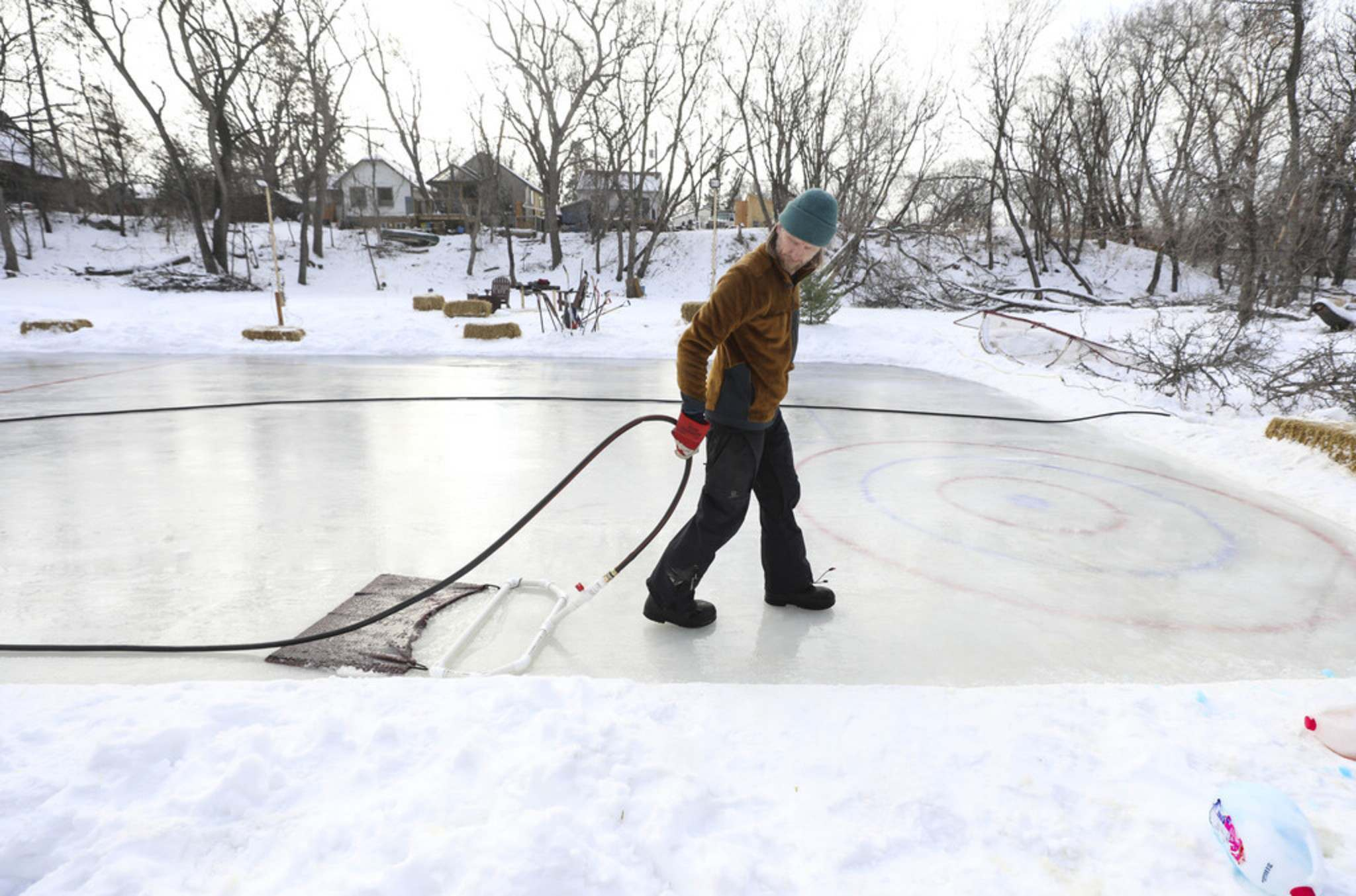RUTH BONNEVILLE / WINNIPEG FREE PRESS  Eric Reder uses a homemade zamboni to flood his rink that he made on the Seine River in front of his home. He can't believe how much work is going into maintenance of the rink because it won't stay frozen — in Winnipeg — in January.