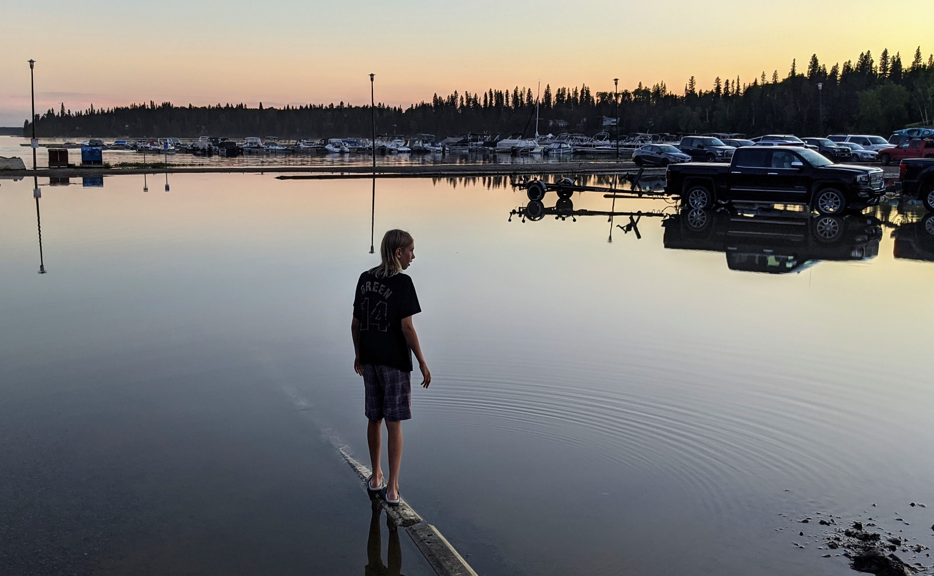 A young boy balances in the shallows of a flood in Paint Lake Provincial Park