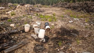 Pails of dirty oil spill onto contaminated ground in Nopiming Provincial Park, violating the law.