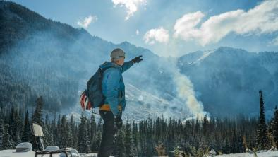 Paul Berntsen stands at the foundation of his yurt, from which he hoped to operate a non-motorized eco-tourism company before his permits were denied. The Silverdaisy peak in Manning Park and a recent clear cut are obscured by smoke from ongoing burning of waste wood. Photo: Fernando Lessa / The Narwhal