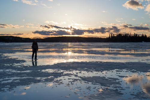 Bearded outdoorsman on melting lake ice, sunset behind him.